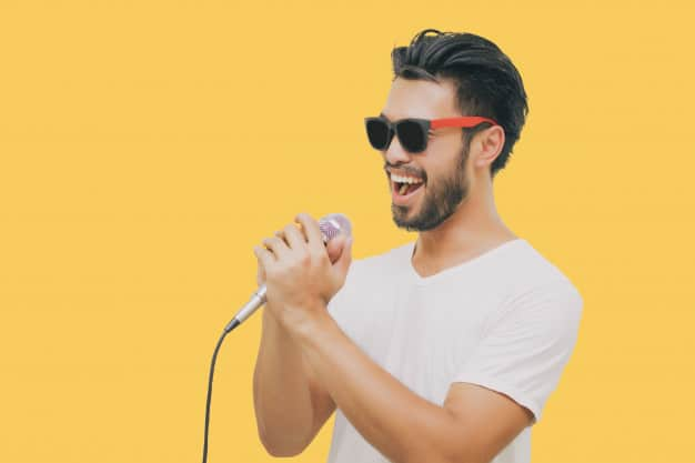 asian-handsome-man-with-mustache-smiling-singing-microphone-isolated-yellow-background_33718-1325