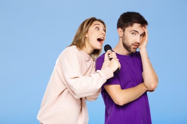 beautiful-couple-blue-wall-girl-singing-microphone-man-didpleased_176420-764