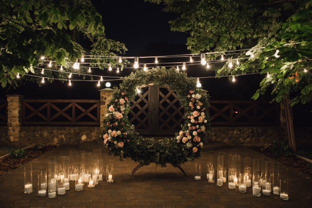 beautiful-photozone-with-big-wreath-decorated-with-greenery-roses-centerpiece-candles-sides-garland-hanged-trees_8353-11019