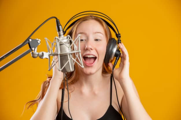 beautiful-redhead-woman-face-singing-with-condenser-silver-microphone-open-mouth-performing-song-pose-yellow-wall-copy-space-your-text-fm-radio-announcer_63135-1253
