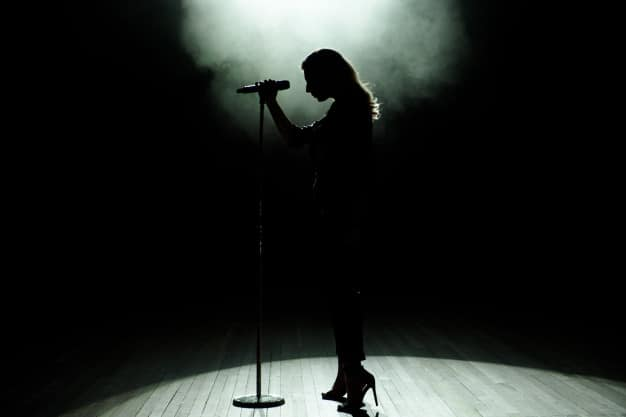 black-silhouette-female-singer-with-white-spotlights-background_104603-1031