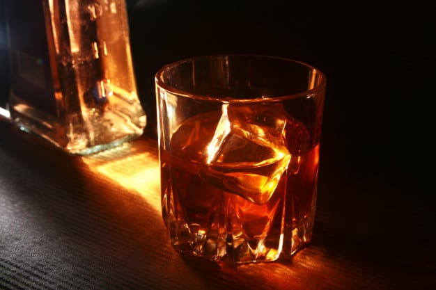 bottle-glass-whiskey-bourbon-with-ice-black-stone-table_93956-337