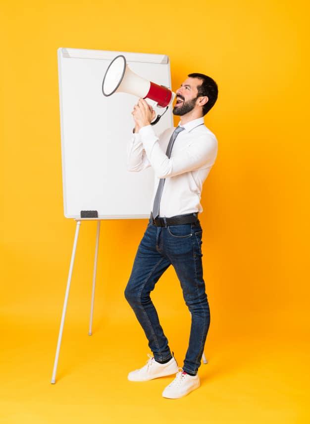 full-length-shot-businessman-giving-presentation-white-board-isolated-yellow-shouting-through-megaphone_1368-60658