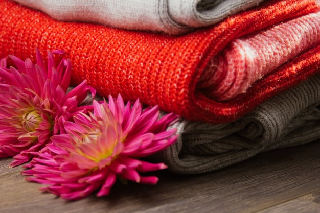 pattern-colorful-knitted-sweaters-closeup-handmade-merino-wool-product-stack-folded-clothes-with-flowers_106652-277