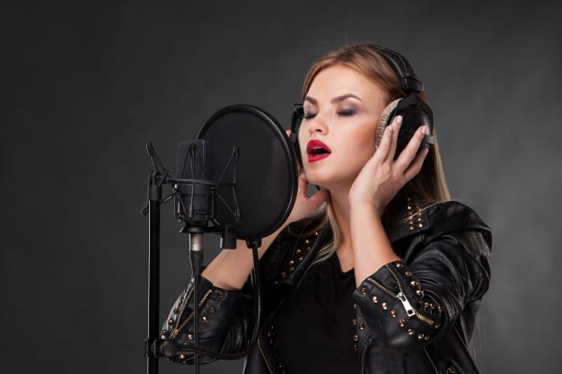 portrait-beautiful-woman-singing-into-microphone-with-headphones_155003-3312