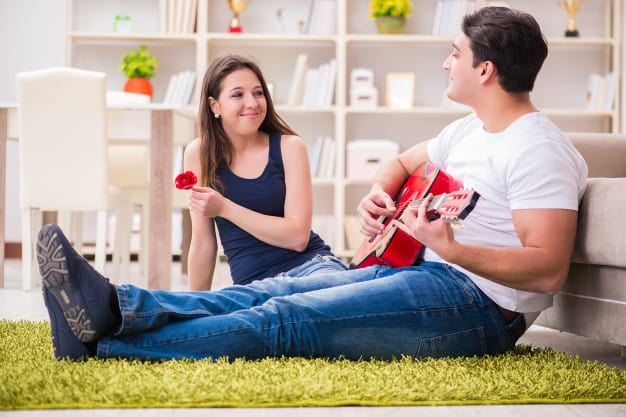 romantic-pair-playing-guitar-floor_85869-9536