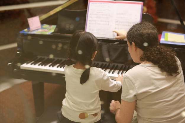 Child having a private tutor on how to play piano