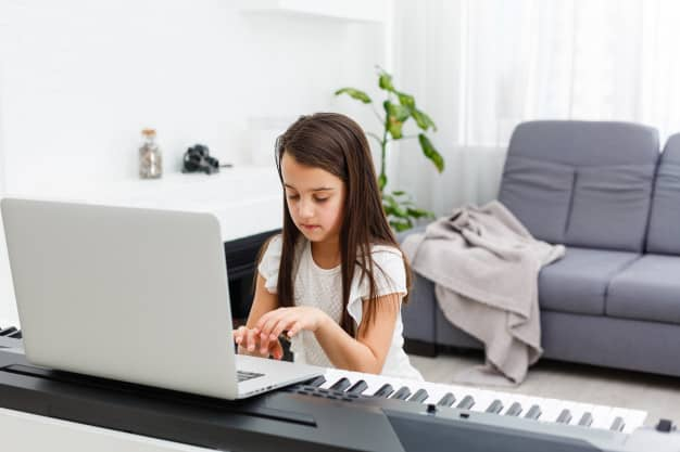 Girl learning how to play a piano online