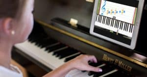 Girl learning how to play piano thru video