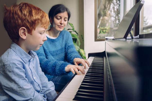 Mother teaching her son on how to play piano