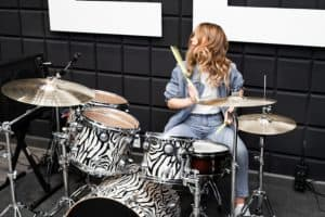 girl playing drums in recording studio