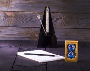 hourglass, metronome and memo pad with a pencil