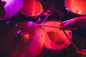 man plays musical percussion instrument with drum sticks
