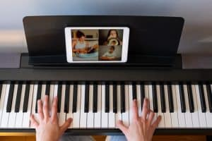 woman having video chat with friends while playing a piano