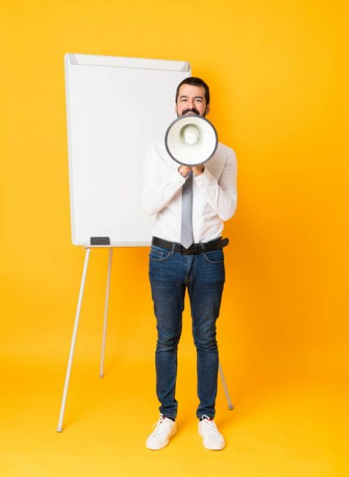 full-length-shot-businessman-giving-presentation-white-board-isolated-yellow-background-shouting-through-megaphone_1368-66127
