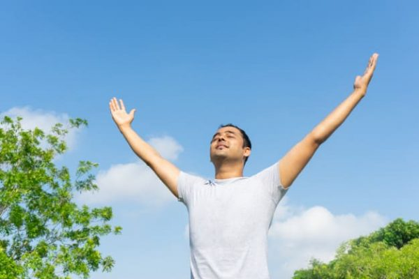 indian-man-concentrating-raising-hands-outdoors-with-blue-sky-green-tree-branches_1262-12684