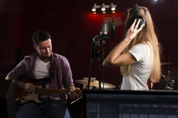 sideways-woman-singing-guy-sitting-with-guitar_23-2148366467