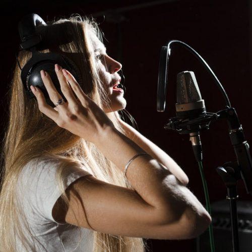 woman-singing-microphone-wearing-headphones_23-2148366442